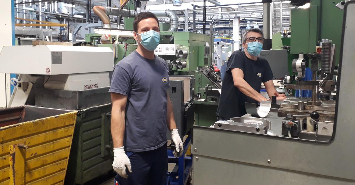 Zwei Mitarbeiter der MIBA-AG mit Mund-Nasen-Schutz während ihrer Arbeit in der Werkstatt