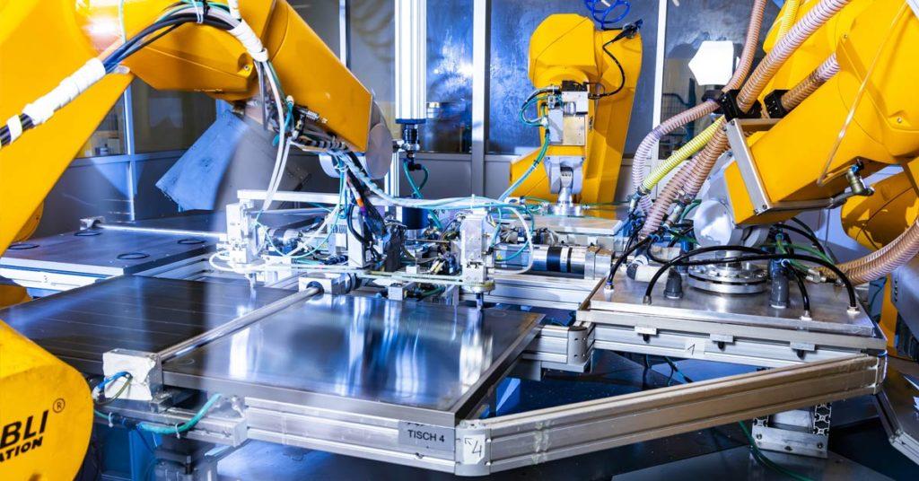 Mehrere Arme von Industrierobotern in einer Montagehalle
