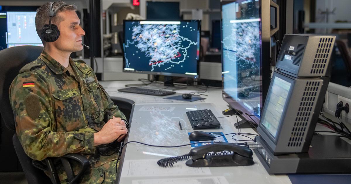 Ein Soldat der Bundeswehr sitzt in einem Kontrollraum vor mehreren Monitoren