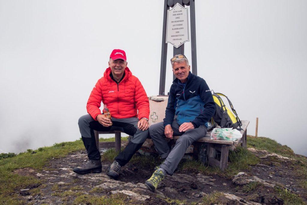 Zwei Männer sitzen vor einem Gipfelkreuz auf einem Berg in Österreich