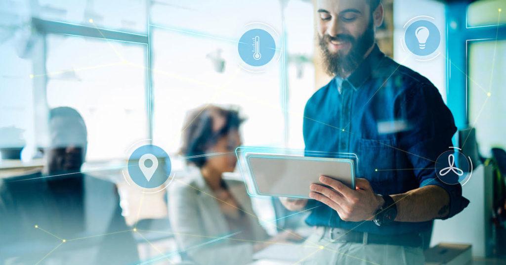 Ein Mitarbeiter eines Büros blickt auf ein Tablet, dass er in der Hand hält, im Hintergrund sitzen eine Frau und ein Mann in Business-Outfits