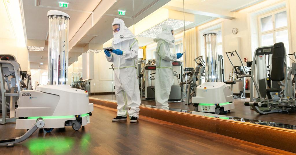 """Ein Reinigungsroboter und eine Person in einem Schutzanzug reinigen ein """"John Harris""""-Fitnessstudio"""