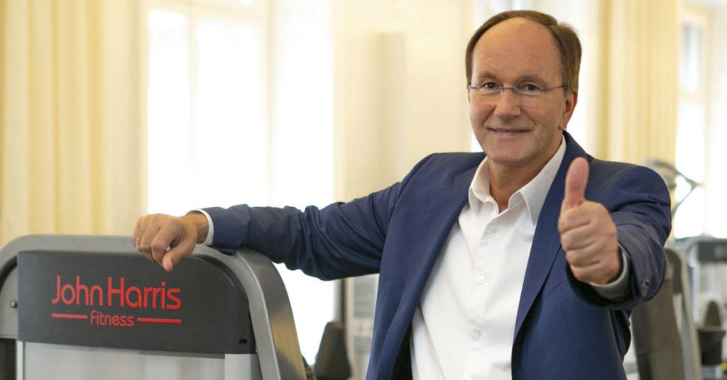 """""""John Harris""""-Geschäftsführer Ernst Minar steh im Fitness-Studio und lächelt in die Kamera"""